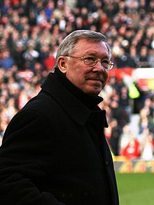 A white-haired man with glasses and a dark overcoat stands on the sideline of a stadium pitch. A stand full with people is visible in the background.