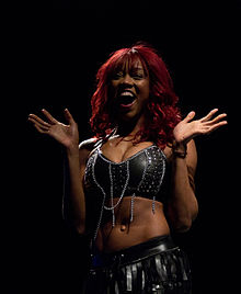 An African-American woman with dyed red hair, wearing a black crop top and black skirt.