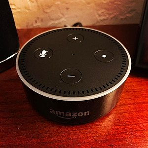 Amazon Echo - The black Amazon Echo Dot (second generation) sitting idle on a wood surface