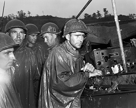 American soldiers of the 77th Infantry Division listen impassively to radio reports of Victory in Europe Day on May 8, 1945. Americans on Okinawa hear of victory in Europe.jpg