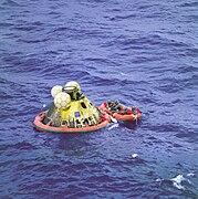 Photographie en couleur de la capsule d'Apollo 11 flottant en mer lors de la récupération des astronautes.