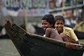Bangladeshi children smile in canoe, Dhaka.jpg