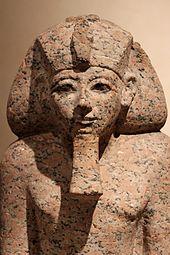 Statua di Hatshepsut con gli attributi faraonici (la barba posticcia, l'ureo) e il copricapo khat. Ägyptisches Museum und Papyrussammlung, Neues Museum, Berlino.