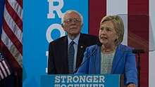 Clinton standing at a podium speaking and looking to her right; Bernie Sanders is standing behind her.