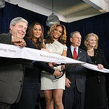 A woman is surrounded by several others, all behind a piece of white tape