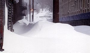 Ground-level view of deep snow and drifts between two city buildings.