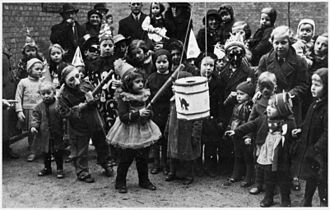 """Fastelavn - Dressed up children engaged in """"slå katten af tønden"""" (Denmark 1937)."""