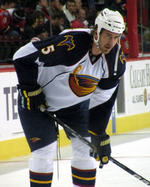 A Caucasian hockey player. He wears a white jersey with dark blue shoulders with a stylized brown thrasher holding a hockey stick logo with the number 5 on his sleeve. He is bent over at the waist leaning on his stick.