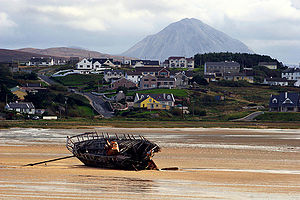 Bunbeg - Bunbeg with Mount Errigal in the background and the wrecked Cara Na Mara (Friend of the Sea) on the tidal sandbanks of Magheraclogher beach. 'Bád Eddie' (Eddie's Boat) ran ashore due to rough seas in the early 70s.