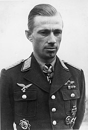 Black-and-white photograph showing the face and upper body of a young man in uniform, his hands behind his back. His hair appears blond and combed to the back. The front right of his jacket bear eagle-and-swastika emblems; the front left of his jacket and the front of his shirt collar bear Iron Cross decorations, black with light outline. He is looking at the camera, his facial expression is secluded.