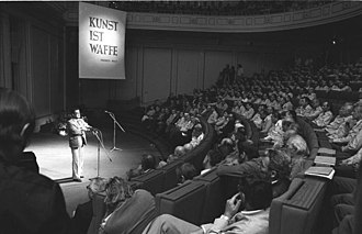 """Konrad Wolf - Konrad Wolf addressing NVA soldiers in 1981, under the motto Kunst ist Waffe (""""art is weapon"""", a quote from his father Friedrich Wolf)."""