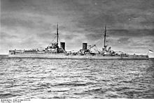 A large gray warship with four large gun turrets and two tall funnels sits idly in harbor.