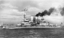 A large warship, thick black smoke pouring out of its rear funnel, steams through the calm sea