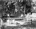 COLLECTIE TROPENMUSEUM Een kampong bij een rivier met een wasman die de was doet in de rivier TMnr 60009697.jpg