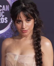 Cabello, with her hair braided, looks forward