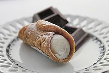 A basic cannolo lightly sprinkled with confectioner's sugar