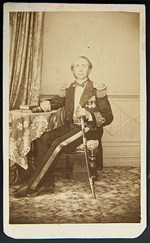 Full-length portrait of seated man at table wearing military uniform and sword