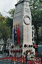 A cuboid granite cenotaph, flanked by red wreaths.
