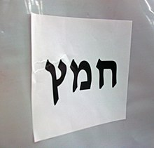 """Chametz"" in large black Hebrew letters on a letter-size piece of paper, affixed horizontally to white plastic background."