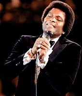 A dark-skinned man wearing a tuxedo, singing into a microphone