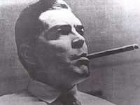 Clean shaven man in shirt and tie with slicked back hair, smoking a long cigar.