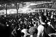 B/W image of hundreds of people orderly sitting outdoors, with an unfurled banner