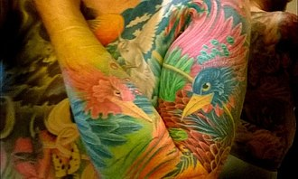 Sleeve tattoo - Close-up of a full sleeve with two phoenixes as part of a full body suit.