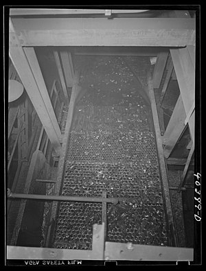 """Coal breaker - Coal being sorted by size and impurities removed on a """"dry"""" screen at the Saint Nicholas breaker near Gilberton, Pennsylvania, in 1938."""