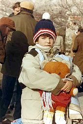 A child wearing winter clothes and holding a large teddy bear looks at the camera, with other similarly dressed adults busy in the background