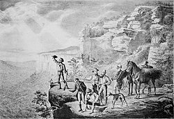 Image shows the group of explorers standing at the edge of a cliff, looking out over plains.