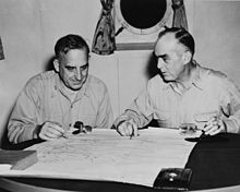 Two men sit at a small table. A map is laid out on the table. Its four corners are held down by a small propeller, a glass, and a book.