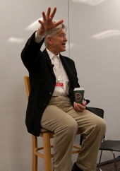 A seated man gesturing while holding a cup of coffee