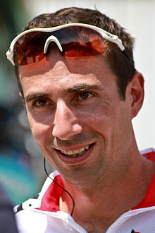 A smiling man in his mid-thirties, with sunglasses on his head, positioned above his eyes.