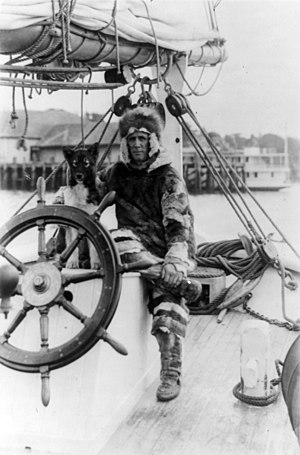 Donald Baxter MacMillan - Donald MacMillan in fur suit at wheel of ship Bowdoin c. 1922