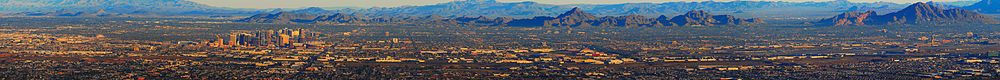 aerial view of the Phoenix skyline, showing the tall buildings of downtown Phoenix to the left of the photo, mountains in the background, the flatness of the rest of the city, with Sky Harbor airport