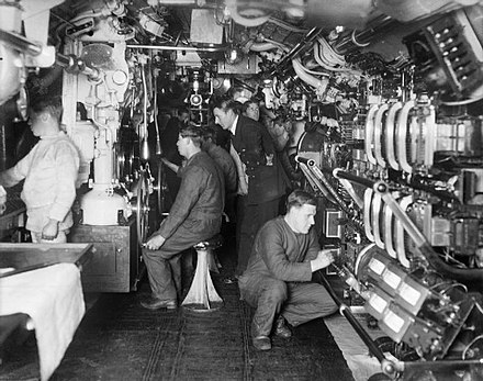 The interior of a British E-class submarine. An officer supervises submerging operations, c. 1914-1918. E class submarine interior IWM Q 18650.jpg