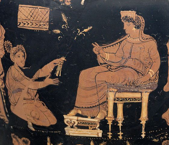Demeter, enthroned and extending her hand in a benediction toward the kneeling Metaneira, who offers wheat, c.340 BCE. (Wikimedia Commons)