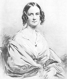Dreiviertel-Porträt einer Frau im Alter von etwa 30 Jahren, mit dunklem Haar in der Mitte, das sich gerade oben teilt und dann auf jeder Seite in Locken fällt.  Sie lächelt angenehm und trägt eine offene Bluse mit einem großen Schal über den Armen