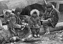 An Inuit family is sitting on a log outside their tent. The parents, wearing warm clothing made of animal skins, are engaged in domestic tasks. Between them sits a toddler, also in skin clothes, staring at the camera, on the mother's back is a baby in a papoose.