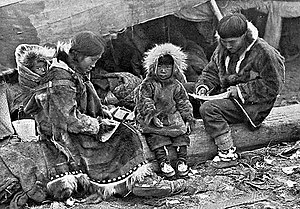 An Inuit family is sitting on a log outside their tent. The parents, wearing warm clothing made of animal skins, are engaged in domestic tasks. Between them sits a toddler, also in skin clothes, staring at the câmera. On the mother's back is a baby in a papoose.