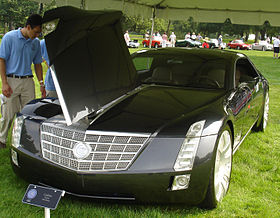 Man looking at Cadillac Sixteen with open hood.
