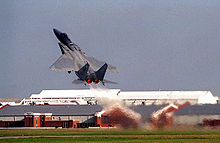 Gray jet fighter taking off at steep angle of attack, with full afterburner, as evident by hot gas ejected from its engines.