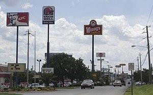 Foto de una carretera en la cual se destacan anuncios de los restaurantes de comida rápida KFC, Wendy's y Taco Bell entre otros. Picture of a highway in which fast food ads are featured:KFC, Wendy's and Taco Bell among others. Taken in Bowling Green, KY..