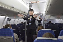 Flight attendants performing a pre-flight safety demonstration on an Aeroflot Sukhoi Superjet.jpg