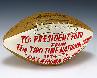 J. C. Watts - A football from the Oklahoma Sooners and signed by the team. Notable signatures include Billy Sims (1978 Heisman Trophy winner) and J. C. Watts. On the white quarter of the football an inscription to Ford was written in red.
