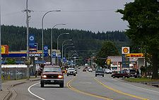 Photo of a three-lane main street in a small town. Visible is a traffic light, sparse traffic, and businesses such as a car lot and gas station.