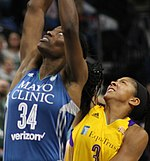 Two very tall women, Fowles at left straining for the ball, Parker beneath her, also straining
