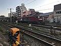 Freight train on Kagoshima Main Line at Sangyo-Daigaku Level Crossing.jpg