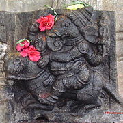 Ganesha riding on his mouse. A sculpture at the Vaidyeshwara temple in Talakkadu, Karnataka, India. Note the red flowers offered by devotees.