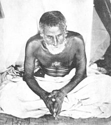 A photograph of a bearded Indian ascetic dressed in dhoti and sitting down cross-legged